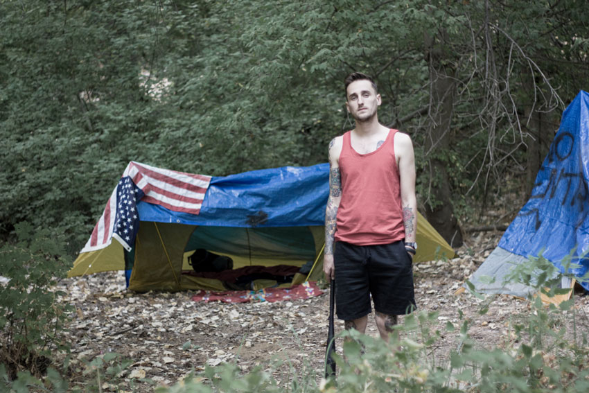 "Phil America standing outside his tent in ""The Jungle"""